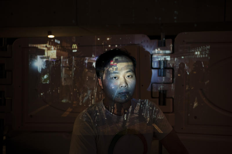 Wong Ho poses for a portrait next to a barricade as a projector displays a photograph, previously taken during the unrest, over him at a protest in Hong Kong. For more than five months, protesters have led a mass movement that prompted the Hong Kong government to withdraw a controversial extradition bill. Following this victory, they have persisted in advocating for their four remaining demands, including calls for democratic reforms and an independent probe into police tactics. (Photo: Felipe Dana/AP)
