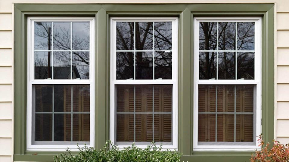 Three new replacement windows with green trim on front of house.