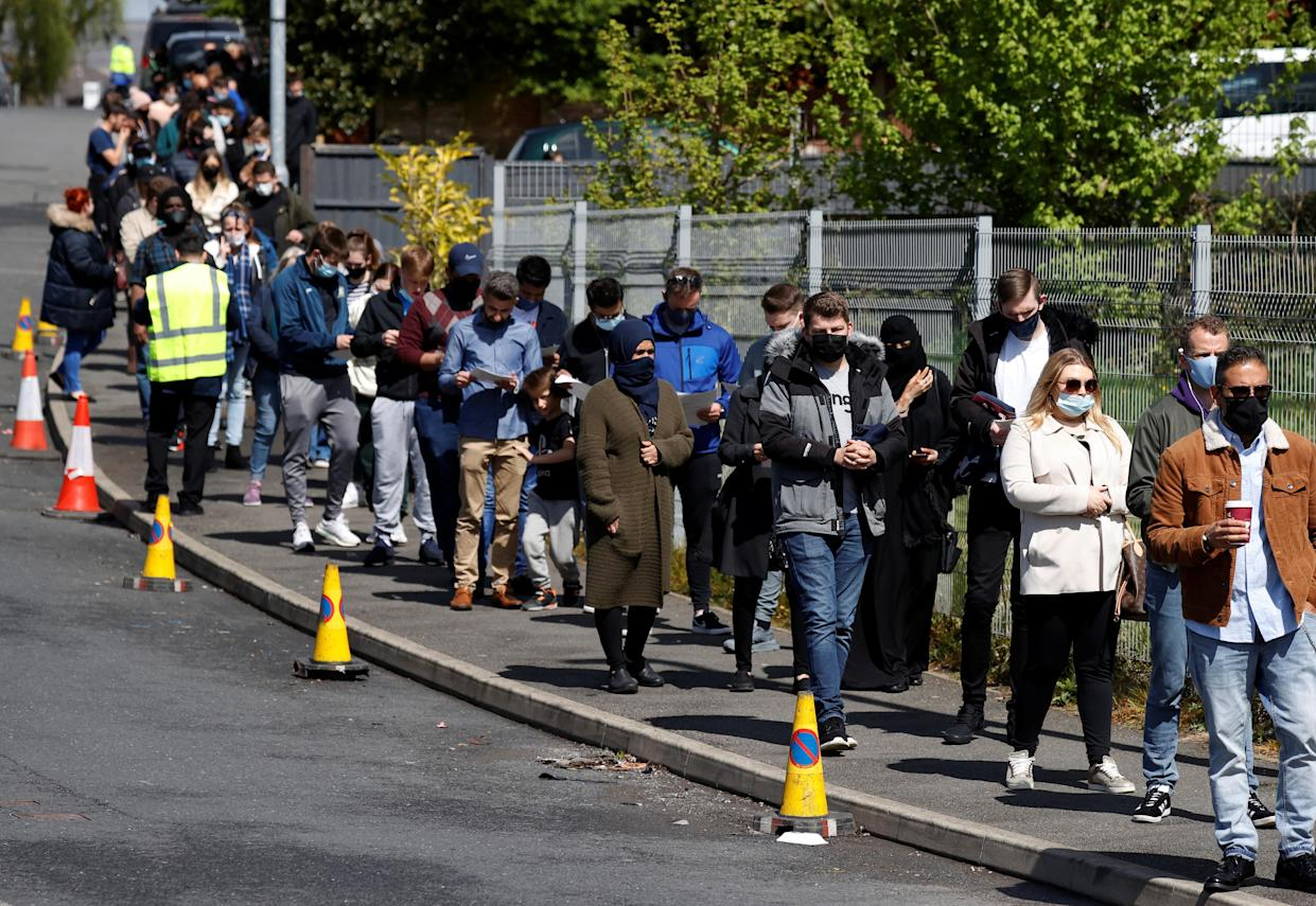 People line up outside a mobile vaccination centre, amid the outbreak of the coronavirus disease (COVID-19) in Bolton, Britain, May 16, 2021. REUTERS/Phil Noble
