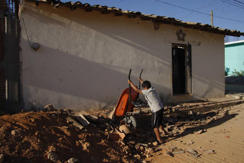 A young resident dumps a wheelbarrow of collected debris onto a pile of rubble, caused by Tuesday's magnitude-7.4 quake, as town residents clean up the damage in San Juan Cacahuatepec, in the Mexican state of Oaxaca, near the border with Guerrero, early Wednesday March 21, 2012. As of Wednesday, there were still no reports of deaths from Tuesday's quake centered near the border between the southern states of Oaxaca and Guerrero, even after 10 aftershocks. (AP Photo/Luis Alberto Cruz Hernandez)