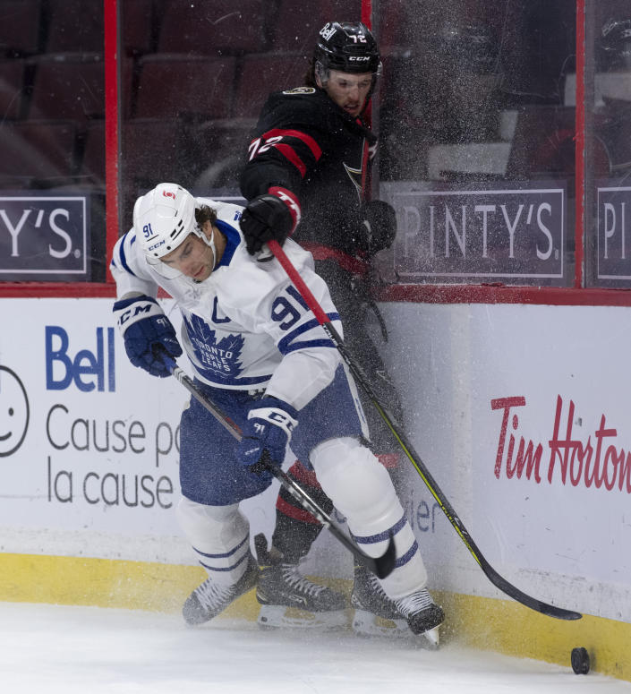 Toronto Maple Leafs center John Tavares knocks Ottawa Senators defenceman Thomas Chabot off the puck during the first period of an NHL hockey game in Ottawa, Ontario, Saturday, Jan. 16, 2021. (Adrian Wyld/The Canadian Press via AP)