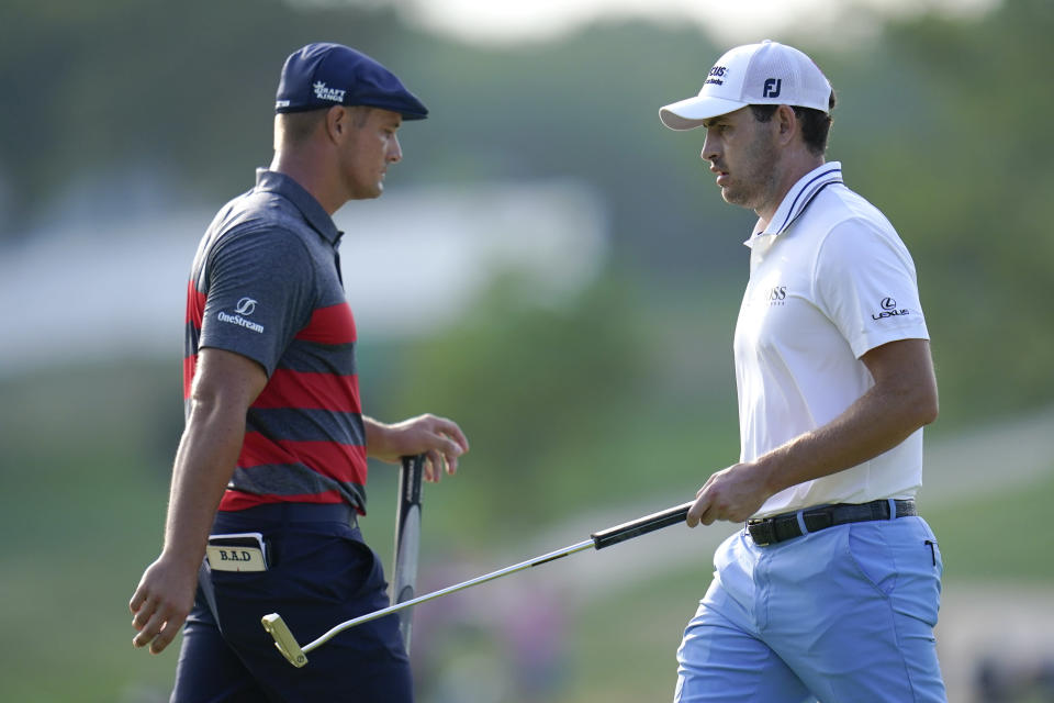Patrick Cantlay, right, walks by Bryson DeChambeau after he sank his putt on the 17th green during the final round of the BMW Championship golf tournament, Sunday, Aug. 29, 2021, at Caves Valley Golf Club in Owings Mills, Md. (AP Photo/Julio Cortez)
