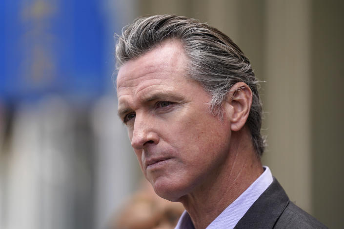 FILE - In this June 3, 2021 file photo, California Gov. Gavin Newsom listens to questions during a news conference outside a restaurant in San Francisco While governors across the country are ending all or most of their coronavirus restrictions, many of them are keeping their pandemic emergency orders in place. Those orders allow them to restrict public gatherings and businesses, mandate masks, sidestep normal purchasing rules, tap into federal money and deploy National Guard troops to administer vaccines. (AP Photo/Eric Risberg, File)