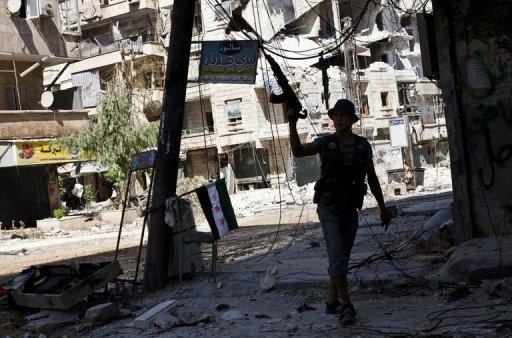 A Syrian rebel walks in a heavily damaged street in the Salaheddin district of the northern city of Aleppo
