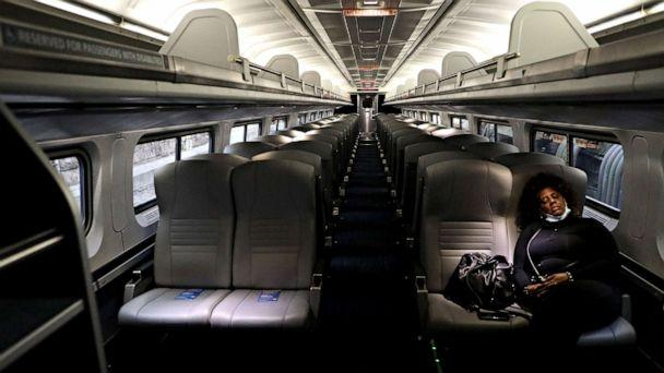 PHOTO: A lone passenger sleeps in an empty Amtrak car as the train pulls into Penn Station, on April 9, 2020, in Baltimore. (Rob Carr/Getty Images)