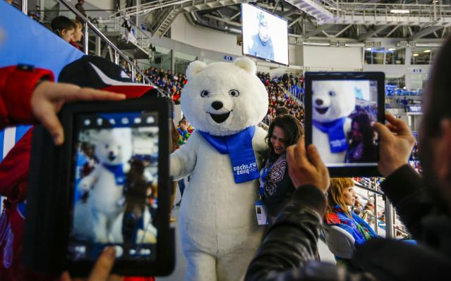 A woman poses with a Sochi Olympic mascot while others take pictures of her during the women's preliminary round ice hockey game between Germany and Sweden at the 2014 Sochi Winter Olympics February 11, 2014. REUTERS/Shamil Zhumatov (RUSSIA - Tags: SPORT OLYMPICS)