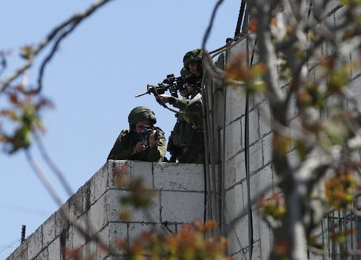 Israeli forces aim their weapons towards Palestinian demonstrators on March 31, 2018 during clashes in occupied West Bank city of Hebron (AFP Photo/HAZEM BADER)