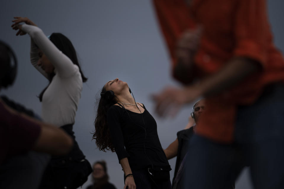 People dance as they take part in a Silent Disco session in front of the sea in Barcelona, Spain, Sunday, April 11, 2021. The silent disco is an event where everyone wears noise-canceling headphones while dancing in a group and respecting social distancing regulations. Participants can choose one of the multiple channels of music to dance to, so they are dancing to different songs at the same time. (AP Photo/Emilio Morenatti)