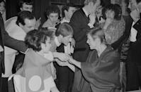<p>Fans flock David Bowie as he and model Viv Lynn arrive at a premiere party for <em>Just a Gigolo </em>at the Cafe Royal in London in 1979. </p>