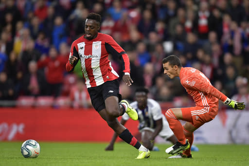 Athletic Bilbao's Inaki Williams goes for the ball in front Valladolid's goalkeeper Masitp before to scoring his goal during the Spanish La Liga soccer match between Athletic Bilbao and Valladolid at San Mames stadium in Bilbao, northern Spain, Sunday, Oct. 20, 2019. (AP Photo/Alvaro Barrientos)