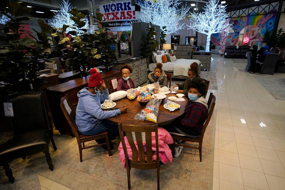 <p>Tiffany Woodley (left) sits at a table with her family after spending the night inside the furniture store. </p>
