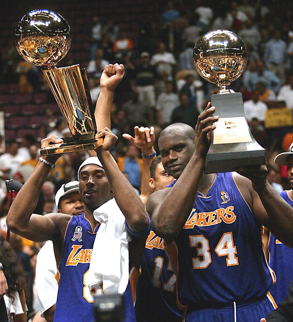 Los Angeles Lakers Kobe Bryant (L) and Shaquille O'Neal (R) hold up the Championship and MVP trophys after game four of the NBA Finals against the New Jersey Nets at Continental Airlines Arena Kobe Bryant 12 June 2002 in East Rutherford, NJ. The Lakers  won their third consecutive title by a score of 113-107  to sweep the best-of-seven series.   AFP PHOTO/Matt CAMPBELL (Photo by MATT CAMPBELL / AFP) (Photo by MATT CAMPBELL/AFP via Getty Images)