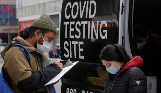 A man signs up to take a COVID-19 test at a mobile testing van in New York City. Experts say the number of actual COVID-19 cases in the U.S. may be higher than the confirmed totals due to testing behaviour in the country.