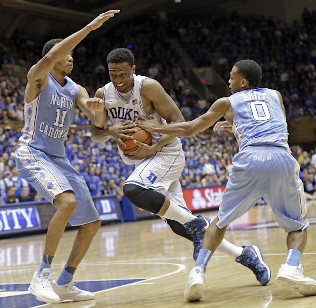 Duke's Jabari Parker drives between North Carolina's Brice Johnson (11) and Nate Britt (0) during the second half of an NCAA college basketball game in Durham, N.C., Saturday, March 8, 2014. Duke won 93-81. (AP Photo/Gerry Broome)