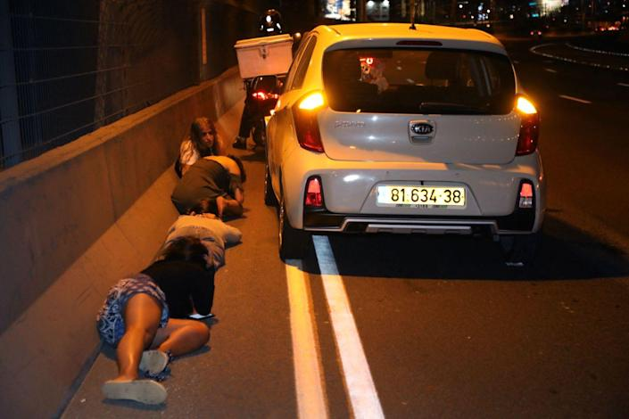 People take cover next to a car on the side of a road