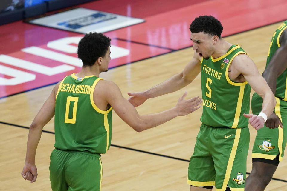 Oregon's Chris Duarte (5) celebrates with Will Richardson (0) after a Duarte dunk during the second half of a second-round game against Iowa in the NCAA men's college basketball tournament at Bankers Life Fieldhouse, Monday, March 22, 2021, in Indianapolis. (AP Photo/Darron Cummings)