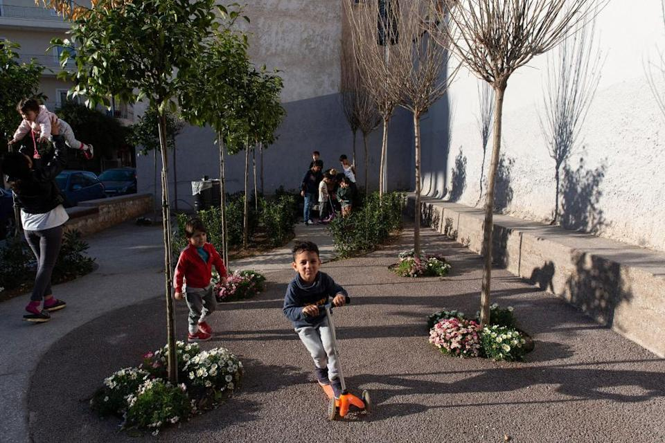 Children play in a pocket park in Kolonos in Athens