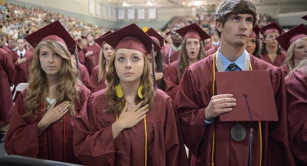 Students  listen to then national anthem prior to US President Barack Obama's  delivering of the commencement address on May 21, 2012 at Missouri Southern State University in Joplin, Missouri. AFP PHOTO/Mandel NGAN        (Photo credit should read MANDEL NGAN/AFP/GettyImages)