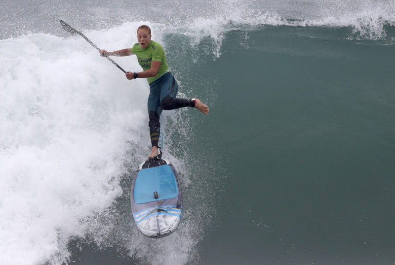 Candice Appleby of the United States rides a wave to win the silver medal in the surfing women's SUP race final during the Pan American Games on Punta Rocas beach in Lima Peru, Friday, Aug.2, 2019. (AP Photo/Silvia Izquierdo)