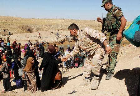 Kurdish Peshmerga forces help people, who fled from their homes in Hawija, as they arrive to be transported to camps for displaced people, in southwest of Kirkuk, Iraq October 4, 2017. REUTERS/Ako Rasheed
