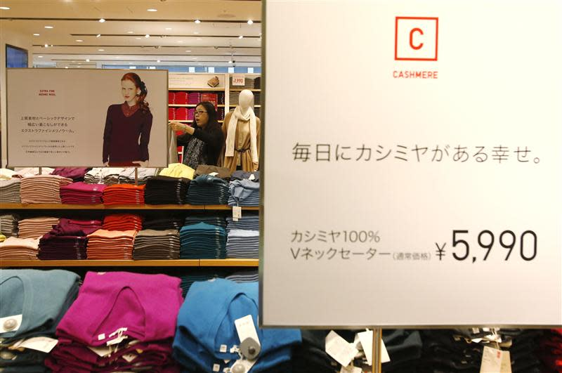 A woman checks cashmere clothes at Fast Retailing's Uniqlo casual clothing store in Tokyo
