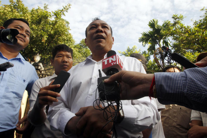 Chan Chen, center, lawyer to Kem Sokha, former leader of now dissolved opposition Cambodia National Rescue Party, talks with the media in front of his home in Phnom Penh, Cambodia, Monday, Sept. 10, 2018. Kem Sokha was released on bail Monday after being jailed for a year on a treason charge, a government spokesman said. A small crowd has gathered outside his home in Phnom Penh but so far he hasn't been seen. His whereabouts are, as yet, unclear. (AP Photo/Heng Sinith)