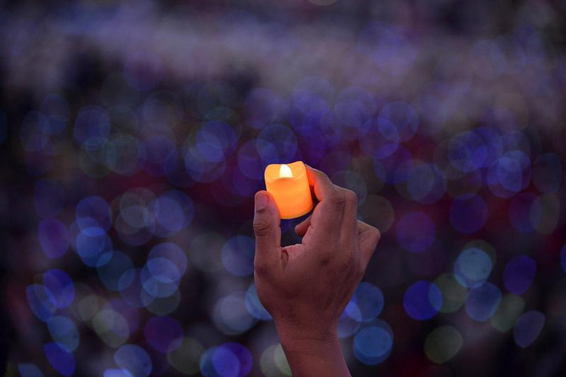 Catholic faithful hold up LED candles as Pope Francis attends a meeting with Filipino families in Manila