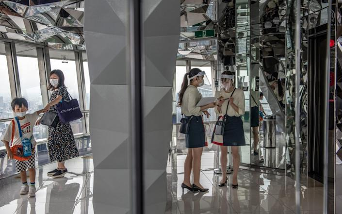 Visitors wearing face masks explore Tokyo Tower - Getty Images Asia