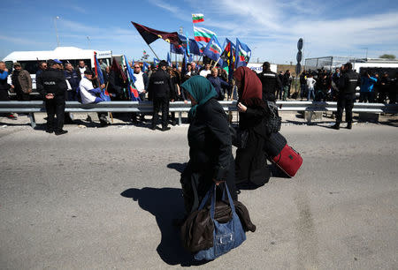 Women carry their luggage as they cross the border crossing between Turkey and Bulgaria on foot during a protest at Kapitan Andreevo border checkpoint, Bulgaria March 24, 2017. Supporters of Bulgarian nationalist parties blocked the crossing in order to prevent ethnic Turkish citizens with Bulgarian passports to vote in the Sunday parliamentary elections. REUTERS/Stoyan Nenov