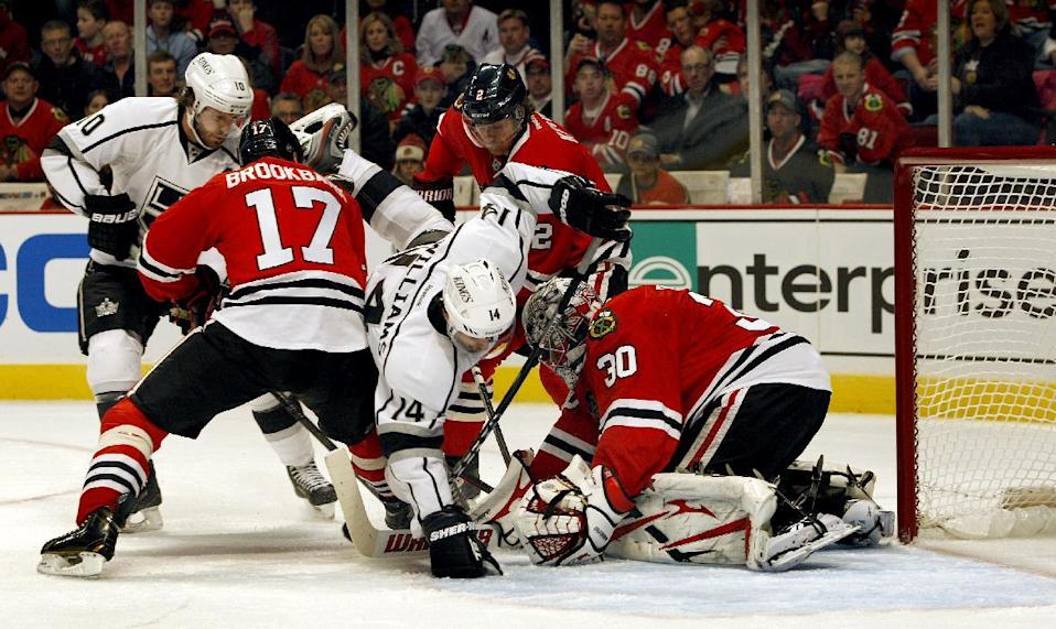 Chicago Blackhawks goalie Ray Emery (30) stops Los Angeles Kings' Justin Williams (14) in front of the goal in the first period of an NHL hockey game, Sunday, Feb. 17, 2013, in Chicago. (AP Photo/John Smierciak)