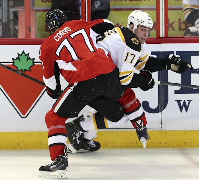 Boston Bruins' Milan Lucic (17) is checked by Ottawa Senators' Joe Corvo (77) during the first period of an NHL hockey game in Ottawa, Ontario on Saturday, Dec. 28, 2013. (AP Photo/The Canadian Press, Fred Chartrand)
