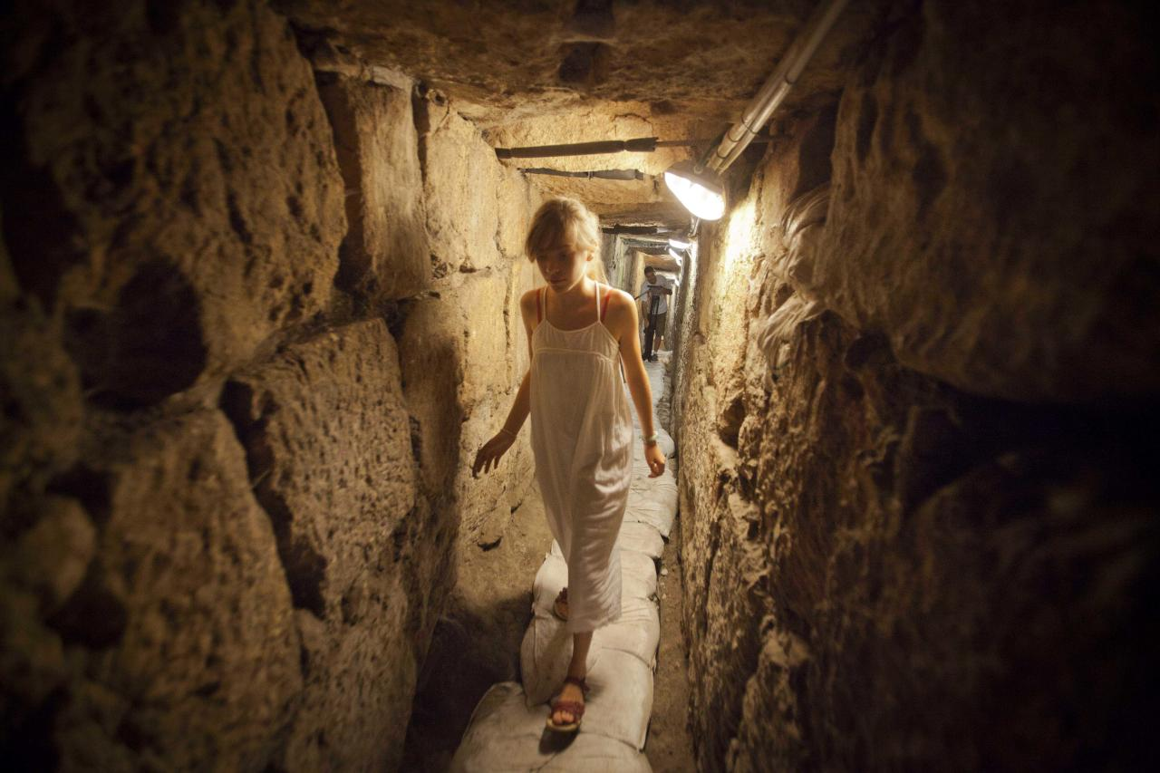 In this picture taken Tuesday, Aug. 2, 2011, a tourist walks through an underground tunnel archaeologists say is a 2,000-year-old drainage tunnel, leading to Jerusalem's Old City. The excavation of an ancient drainage tunnel beneath Jerusalem has yielded new artifacts from a war here 2,000 years ago, archaeologists said Monday, Aug. 8, 2011, shedding light on a key episode of the past buried under today's politically combustible city. (AP Photo/Dan Balilty)