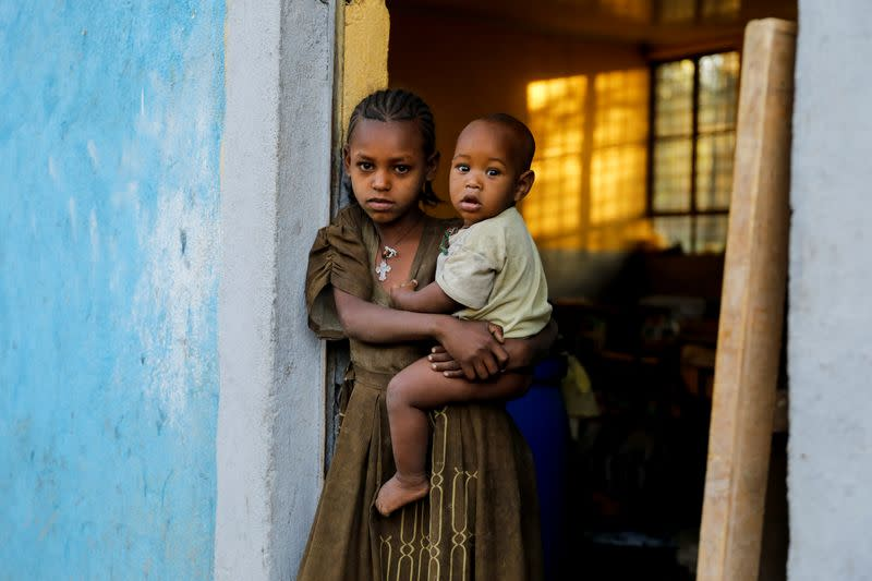 FILE PHOTO: An 11-year-old girl holds her one-year-old brother in the town of Shire in theTigray region of Ethiopia.