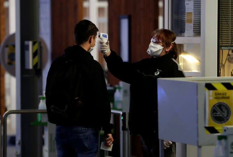 A man gets his temperature taken at Skoda Auto's factory as employees return to work after the company restarted production following a shutdown last month due to the coronavirus disease (COVID-19) outbreak in Mlada Boleslav