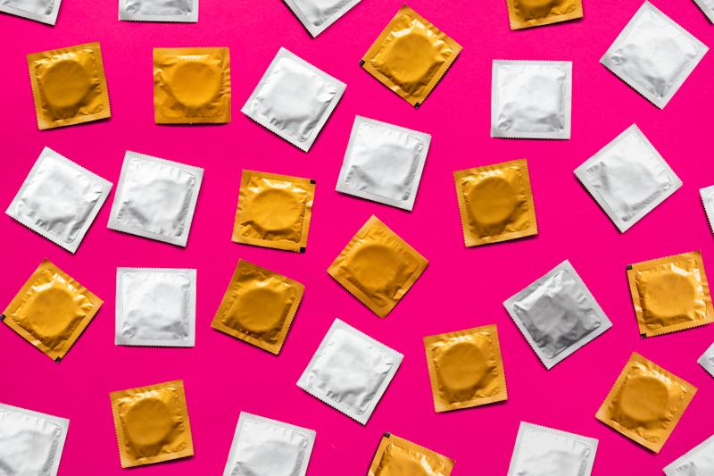 Directly Above Shot Of Condom Packets Over Pink Background