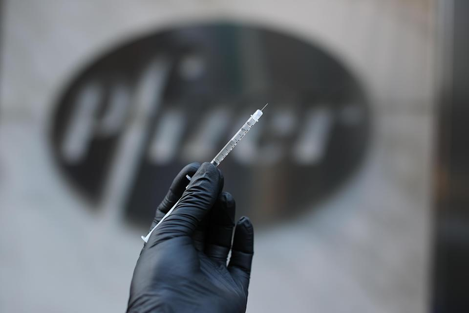 NEW YORK, USA - NOVEMBER 19: A syringe is seen by the logo of Pfizer's headquarter in Manhattan, New York City, United States on November 19, 2020. According the pharmaceutical giant Pfizer on Wednesday that new Pfizer results for COVID-19 vaccine is safe and 95% effective. (Photo by Tayfun Coskun/Anadolu Agency via Getty Images)