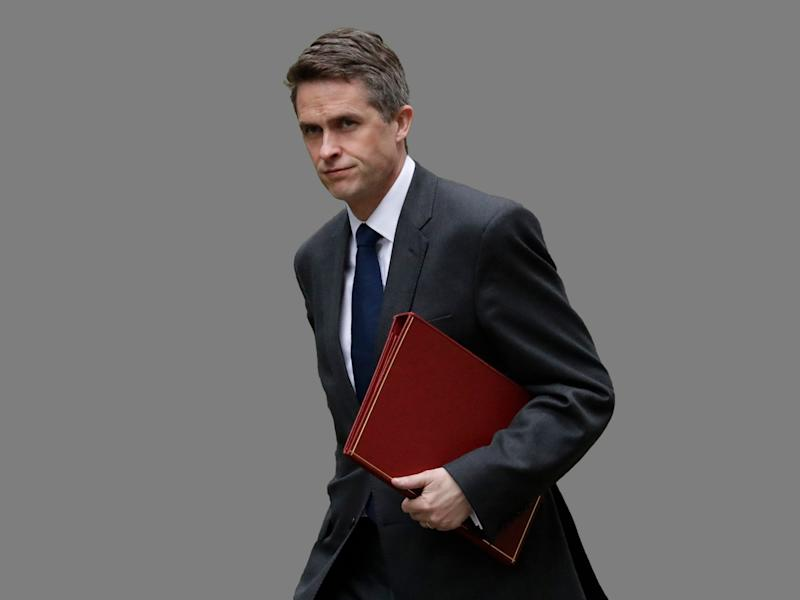 Gavin Williamson headshot, as Britain Defense Secretary, graphic element on gray