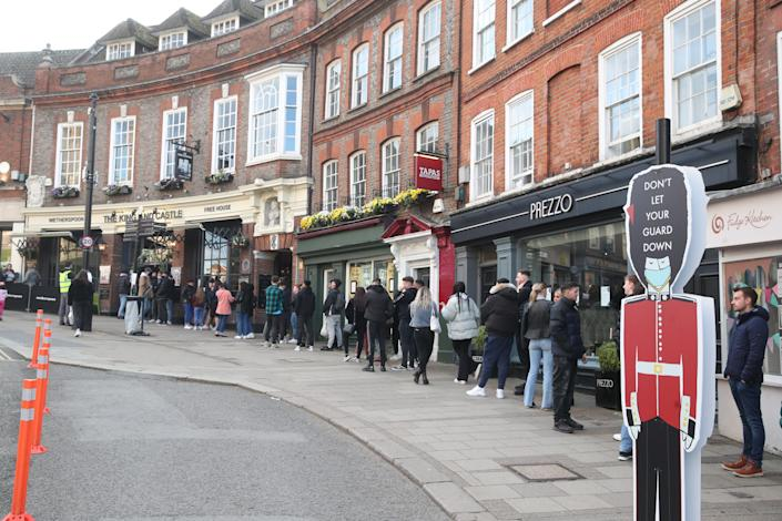 People queue outside Wetherspoon's, King and Castle pub in Windsor, following the further easing of lockdown restrictions in England. Picture date: Friday April 16, 2021.