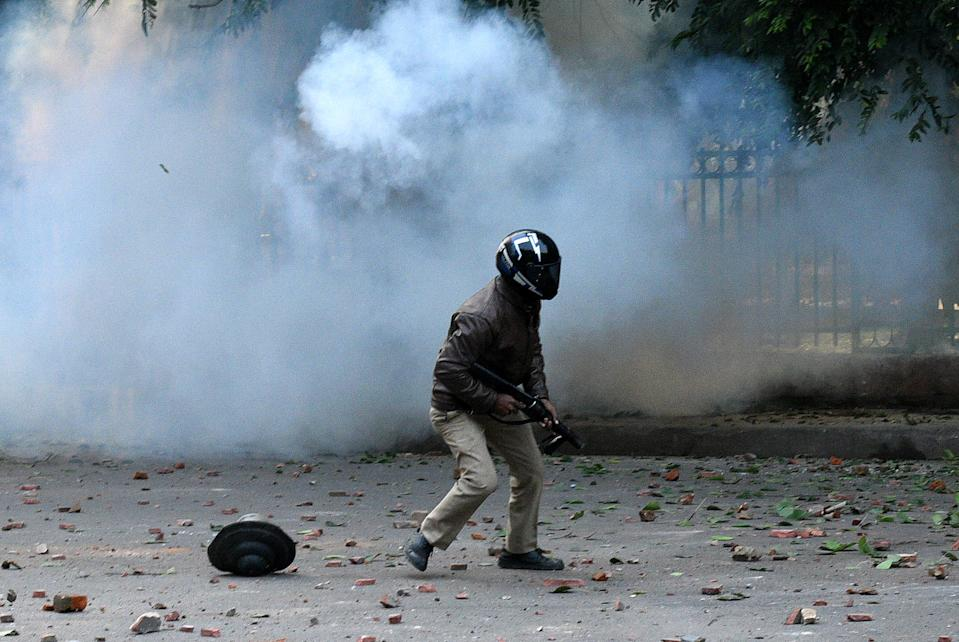 LUCKNOW, INDIA - DECEMBER 19: Police personnel fire tear gas shells towards demonstrators during an anti Citizenship Amendment Act (CAA) and National Register of Citizens (NRC) protest at Parivartan Chowk area on December 19, 2019 in Lucknow, India. The act seeks to grant Indian citizenship to refugees from Hindu, Christian, Sikh, Buddhist and Parsi communities fleeing religious persecution from Pakistan, Afghanistan, and Bangladesh, and who entered India on or before December 31, 2014. The Parliament had passed the Citizenship (Amendment) Bill, 2019 last week and it became an act after receiving assent from President Ram Nath Kovind. Since then, protests including some violent ones have erupted in various regions of the country, including the North East over the amended citizenship law. (Photo by Dheeraj Dhawan/Hindustan Times via Getty Images)