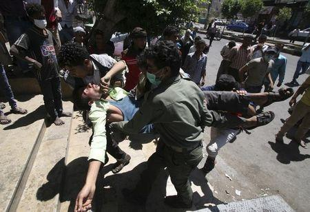 Anti-Houthi protesters carry a fellow demonstrator who sustained injuries after pro-Houthi police troopers opened fire to disperse them in Taiz March 25, 2015. REUTERS/Anees Mahyoub