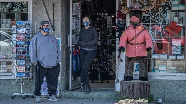People standing outside a storefront in the ByWard Market on March 17.