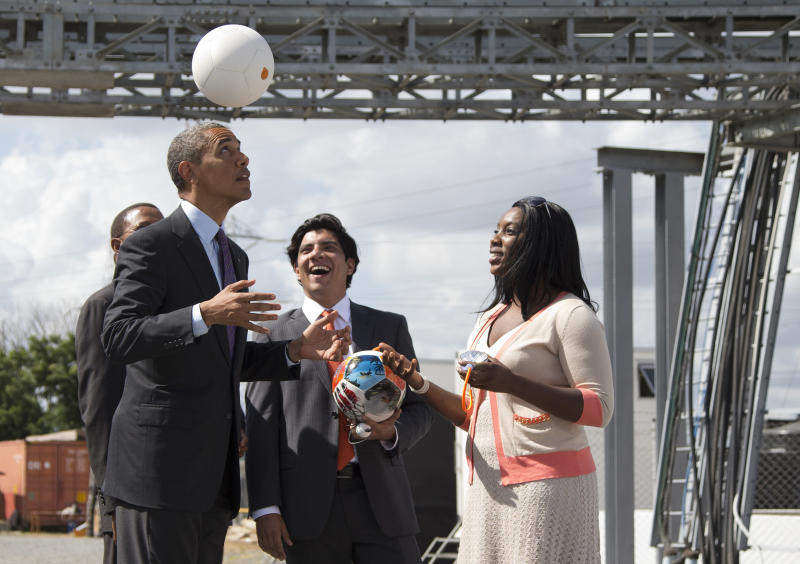 """U.S. President Barack Obama demonstrates """"the Soccket Ball,"""" which uses kinetic energy to provide power to charge a cell phone or power a light, during an event at the Ubungo power plant to promote energy innovation on Tuesday, July 2, 2013, in Dar Es Salaam, Tanzania. The president is traveling in Tanzania on the final leg of his three-country tour in Africa. (AP Photo/Evan Vucci)"""