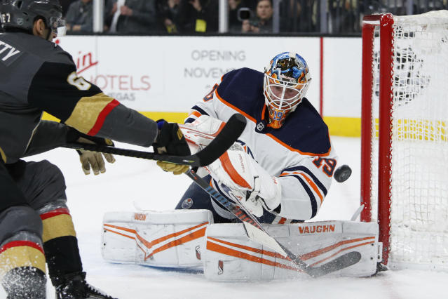 Edmonton Oilers goaltender Mikko Koskinen (19) knocks the puck away from the Vegas Golden Knights during the second period of an NHL hockey game Wednesday, Feb. 26, 2020, in Las Vegas. (AP Photo/John Locher)