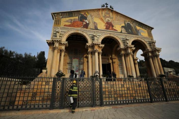 An Israeli firefighter stands outside the Church of All Nations next to the Garden of Gethsemane after a man tried to set a fire inside the Church