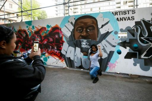 "A woman kneels and raises a fist as she poses in front of a mural of George Floyd in Toronto's ""Graffiti Alley"""