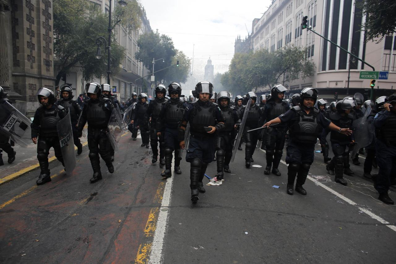 Riot policemen walk towards the Zocalo after protesters had been given a deadline to evacuate the Zocalo in Mexico City