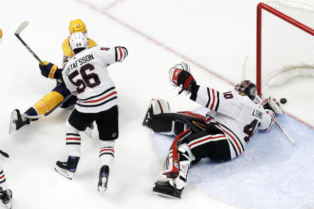 Nashville Predators center Nick Bonino, top left, scores a goal against Chicago Blackhawks goaltender Robin Lehner (40), of Sweden, and defenseman Erik Gustafsson (56), of Sweden, during the first period of an NHL hockey game Tuesday, Oct. 29, 2019, in Nashville, Tenn. Bonino scored all three of Nashville's goals as the Predators won 3-0. (AP Photo/Mark Humphrey)