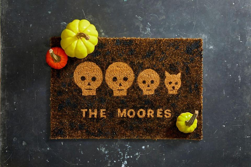 """<p>To give your doormat a Halloween update, <a href=""""https://hmg-prod.s3.amazonaws.com/files/ghkhalloween-doormatstencils-1564426473.pdf?tag=syn-yahoo-20&ascsubtag=%5Bartid%7C10055.g.421%5Bsrc%7Cyahoo-us"""" rel=""""nofollow noopener"""" target=""""_blank"""" data-ylk=""""slk:download this skull family template"""" class=""""link rapid-noclick-resp""""><strong>download this skull family template</strong></a>. Print out as many faces as you have people in household. Use an X-Acto knife or craft knife to cut out faces, eyes, noses, and mouths. Then, arrange the faces as you want them to appear on your mat, adding cut-out letters if you wish. Attach paper to the doormat with folded-up painter's tape on the back. Then, starting with a little paint at a time, dab paint around the stencil with a foam brush. Continue until the entire mat is covered, and let dry completely before you remove the stencils. </p>"""
