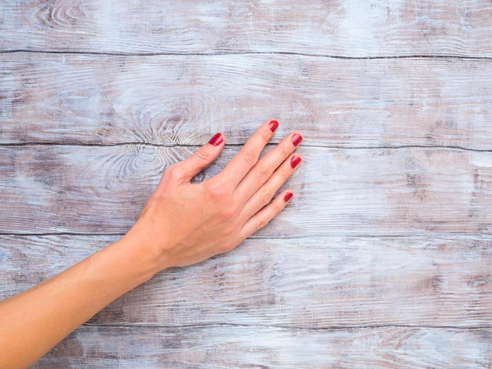 Hand of a woman with red polish on wooden surface