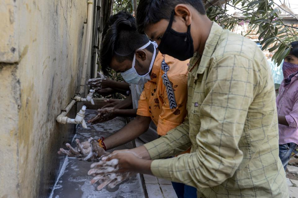 Students wearing facemasks wash their hands before attending a class at a governement-run high school in Secunderabad, the twin city of Hyderabad, on March 4, 2020, as part of health measures taken against the COVID-19 coronavirus outbreak. - The new coronavirus that emerged in a Chinese market at the end of last year has killed 2,981 with more than 80,200 people infected in total, the National Health Commission said. (Photo by NOAH SEELAM / AFP) (Photo by NOAH SEELAM/AFP via Getty Images)